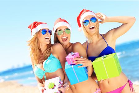 personas reunidas: Una imagen de un grupo de mujeres en bikini y los sombreros de Santa celebración de regalos en la playa