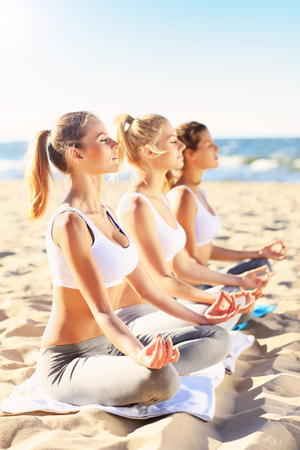 jovenes felices: A picture of a group of women practising yoga on the beach