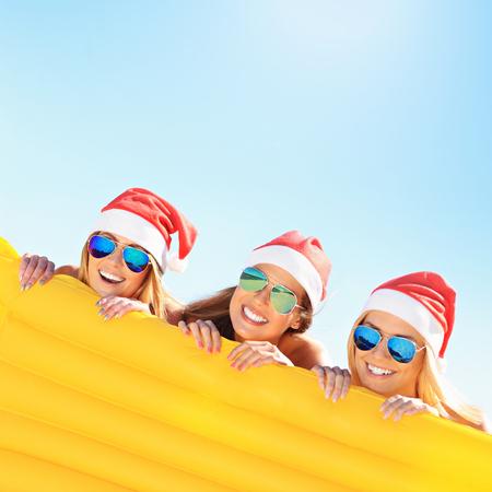 Een foto van een groep vrouwen in bikini en Santa hoeden houden matras op het strand