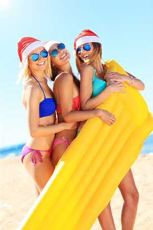 sexy christmas: A picture of a group of women in bikini and Santas hats holding mattress on the beach Stock Photo