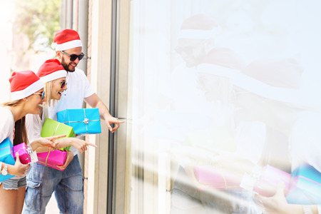 gift boxes: A picture of group of friends in Santas hats sitting in the city with presents