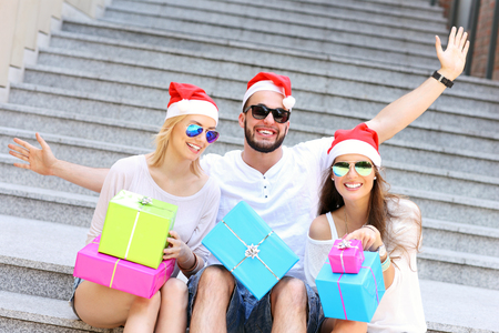 christmas hats: A picture of group of friends in Santas hats sitting in the city with presents
