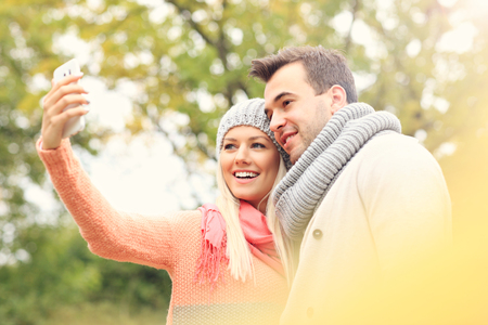 romantic hug: A picture of a young romantic couple with smartphone in the park in autumn
