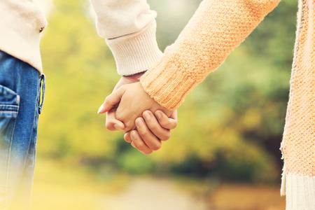 manos agarrando: Una foto de una pareja de la mano en el parque