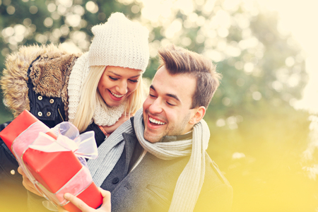 A picture of a young couple with a present in the park Stockfoto