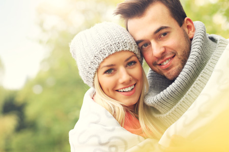 beautiful smile: A picture of a young romantic couple covered with blanket in the park in autumn