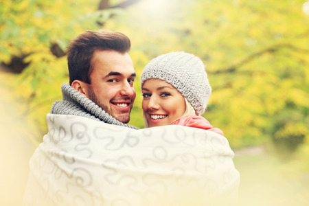couple nature: A picture of a young romantic couple covered with blanket in the park in autumn