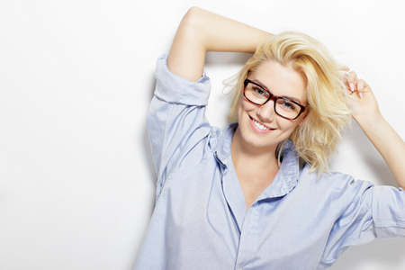 glasses model: A picture of a happy woman posing against the wall