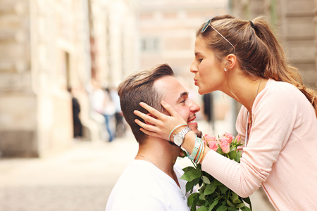A picture of a young romantic couple with flowers in the city Reklamní fotografie