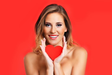 nude adult: A picture of a sexy Valentine woman holding a heart over red background