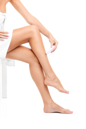 A picture of a sensual woman shaving legs over white background