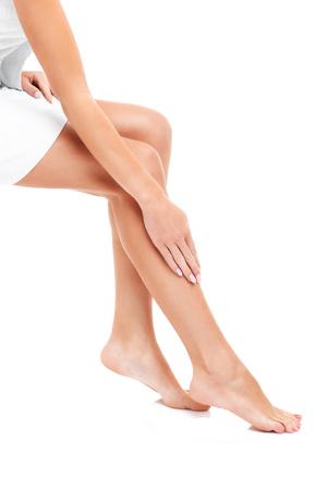 vertical: Una imagen de una mujer sensual que afeita las piernas sobre el fondo blanco