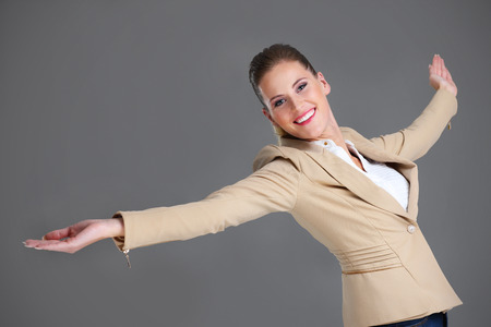 flying woman: Picture of cheerful businesswoman over grey background