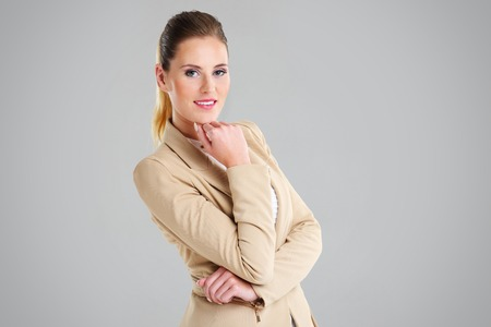 woman portrait: Midsection of happy businesswoman with her arms folded over grey background