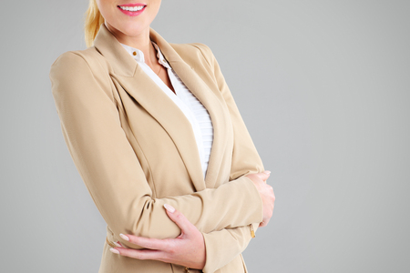 midsection: Midsection of happy businesswoman with her arms folded over grey background