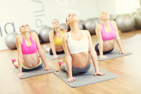 pesas: Imagen del grupo de mujeres que se extiende en el gimnasio