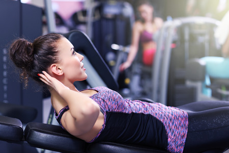 ups: Picture of fit woman doing sit ups in gym Stock Photo