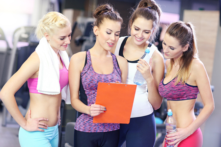 sports club: Group of women discussing plan with personal trainer in gym
