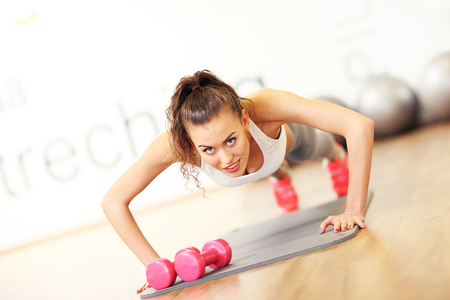 body pump: Picture of young fit woman doing push ups in gym