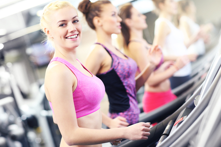 women working out: Group of fit women working out on treadmill in gym