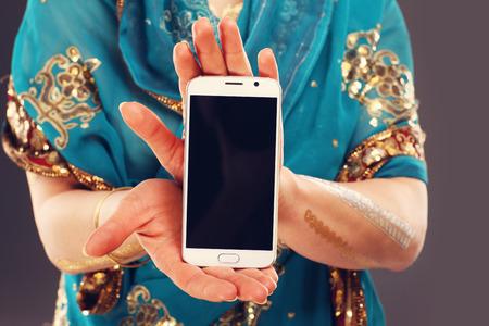 llamando: Sección media de mujer que sostiene teléfono inteligente oriental