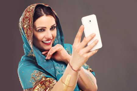 bollywood woman: Portrait of oriental woman using smartphone