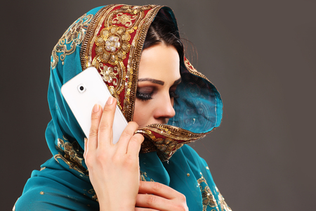 arab glamour: Portrait of oriental woman talking on smartphone Stock Photo
