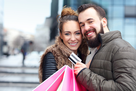 shopping card: Picture of young couple with shopping bags and credit card in the city