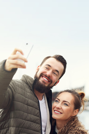 young happy couple: Picture of young couple taking selfie Stock Photo