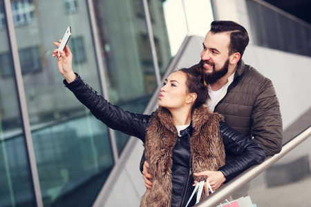 happy shopping: Picture of happy couple huggingand taking selfie while shopping