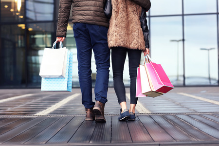 midsection: Midsection of couple with shopping bags in city Stock Photo