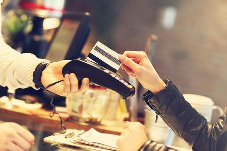 레스토랑에서 신용 카드로 지불하는 여자의 그림