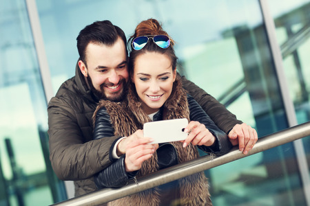 mobile internet: Picture of young couple hanging out in city and taking selfie