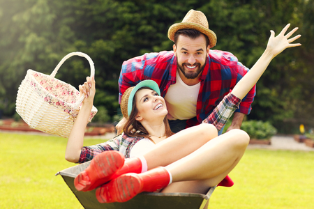 couple having fun: Picture of young couple having fun in the garden riding a barrow Stock Photo