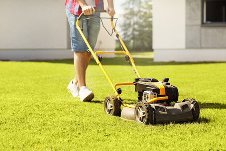 garden lawn: Picture of a young man mowing the lawn