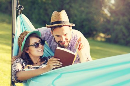 personas leyendo: Fotografía de una pareja romántica relajante en hamaca