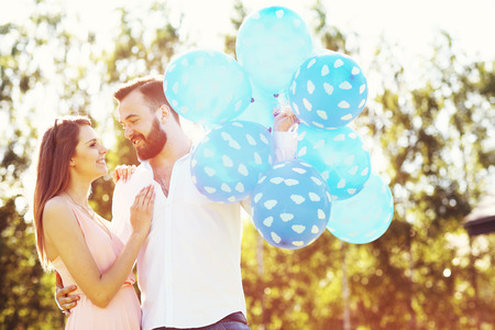 baloons: A picture of romantic couple standing outside with baloons