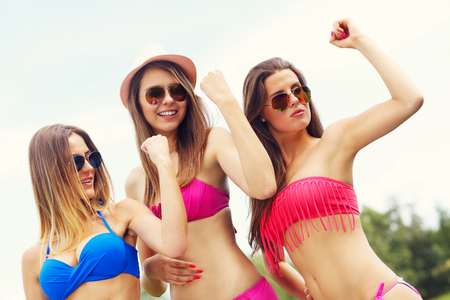showing muscles: Picture presenting group of women in bikini showing muscles outdoors