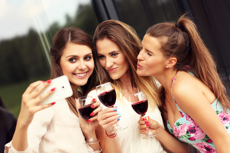 bff: Picture presenting happy group of friends with red wine taking selfie Stock Photo