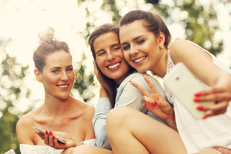 bff: Picture presenting happy group of friends with smartphones sitting outdoors Stock Photo
