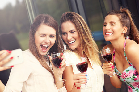 Picture presenting happy group of friends with red wine taking selfie Archivio Fotografico
