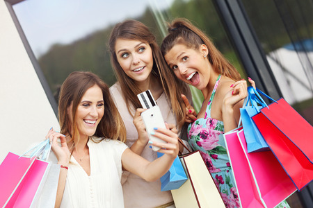 happy shopping: Picture presenting group of girlfriends shopping in the city with credit card and smartphone