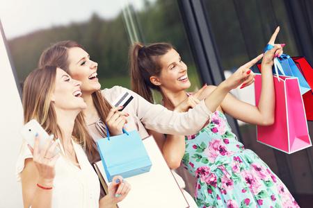 Foto de grupo de amigas presentación de compras por la ciudad con tarjeta de crédito y el teléfono inteligente