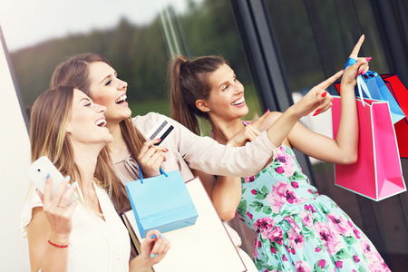 Picture presenting group of girlfriends shopping in the city with credit card and smartphone