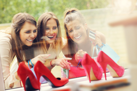cc: Picture presenting group of girlfriends shopping for shoes in the city with credit card