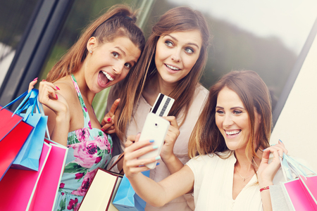 cc: Picture presenting group of girlfriends shopping in the city with credit card and smartphone