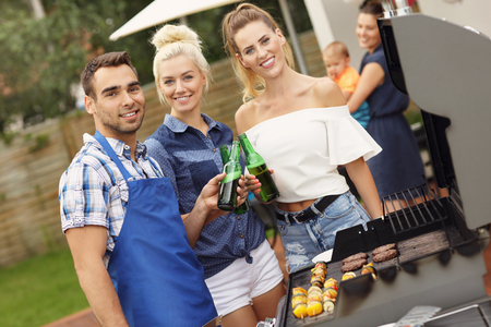 Picture presenting group of friends having barbecue party photo