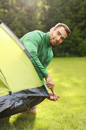 putting up: Picture of young man putting up tent in the forest