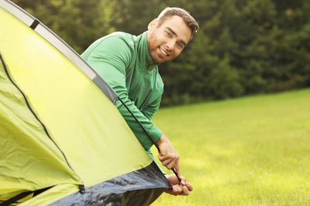 pitching: Picture of young man putting up tent in the forest