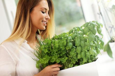 perejil: Imagen de mujer joven con hierbas en la cocina Foto de archivo